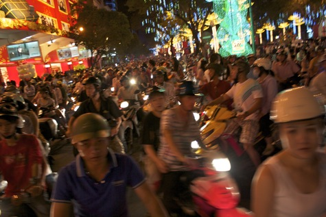 Crossing a wide sea of motorbikes, Saigon, Vietnam