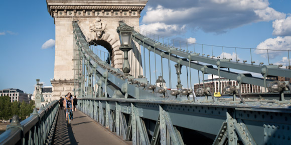 Local person biking across Szechenyi Chain Bridge, Budapest