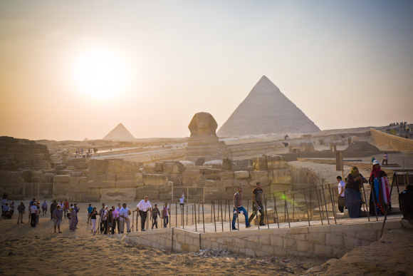 The Great Sphinx and 3 pyramids in the background at sunset