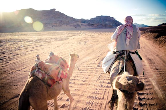 Camel ride in the desert at sunset, Jordan